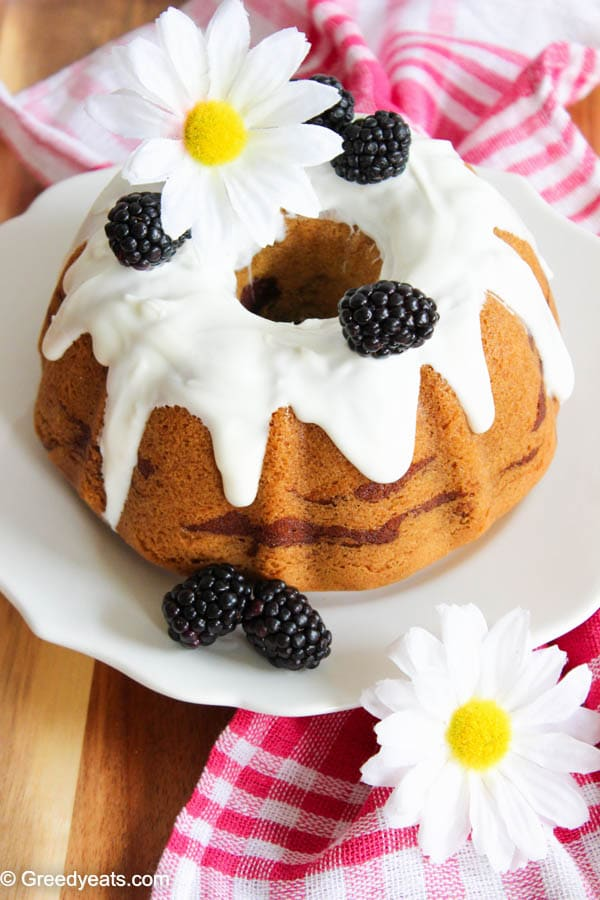 vanilla bundt cake recipe with berry swirls and vanilla icing