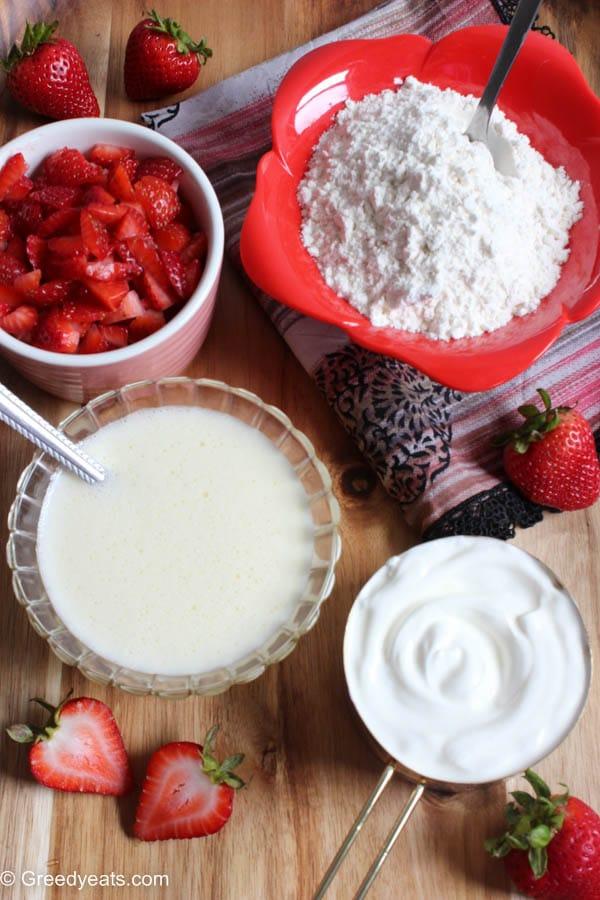 Ingredients like freshly chopped strawberries, flour, yogurt and sour cream to bake bread.