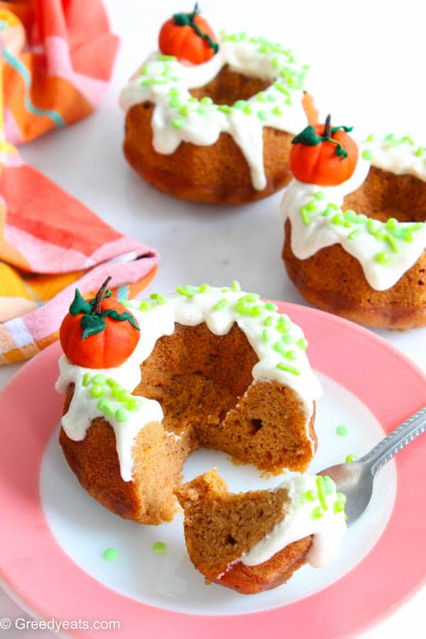 Moist and loaded with fall flavors, mini Pumpkin Bundt Cakes on a pink plate.
