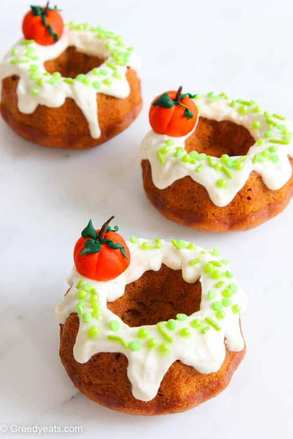 Mini Pumpkin Cakes with cream cheese icing, fall sprinkles and pumpkin toppers.