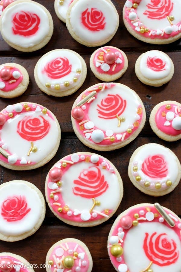 Soft sugar cookies topped with easy royal icing and rose gold sprinkles. Find recipe for these pretty rose cookies on greedyeats.com
