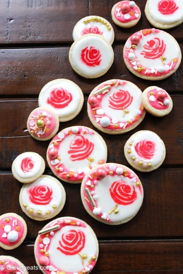 Soft, buttery and melt in your mouth rose cookies for valentines day! These are frosted with an easy royal icing and sprinkles for a little crunch.
