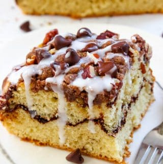 Simple and delicious cinnamon coffee cake recipe with buttery cinnamon crumb topping, a delicious layer of chocolate and some sweet vanilla glaze! Recipe on Greedyeats.com