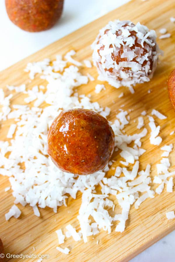 Carrot balls rolling in coconut flakes.
