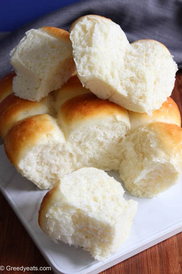 Soft, fluffy, buttery and the best homemade dinner rolls recipe made with pantry staples. Recipe on Greedyeats.com
