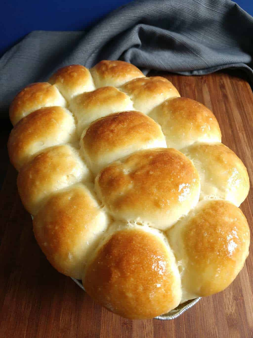 Baked dinner rolls in baking pan, topped with melted butter.