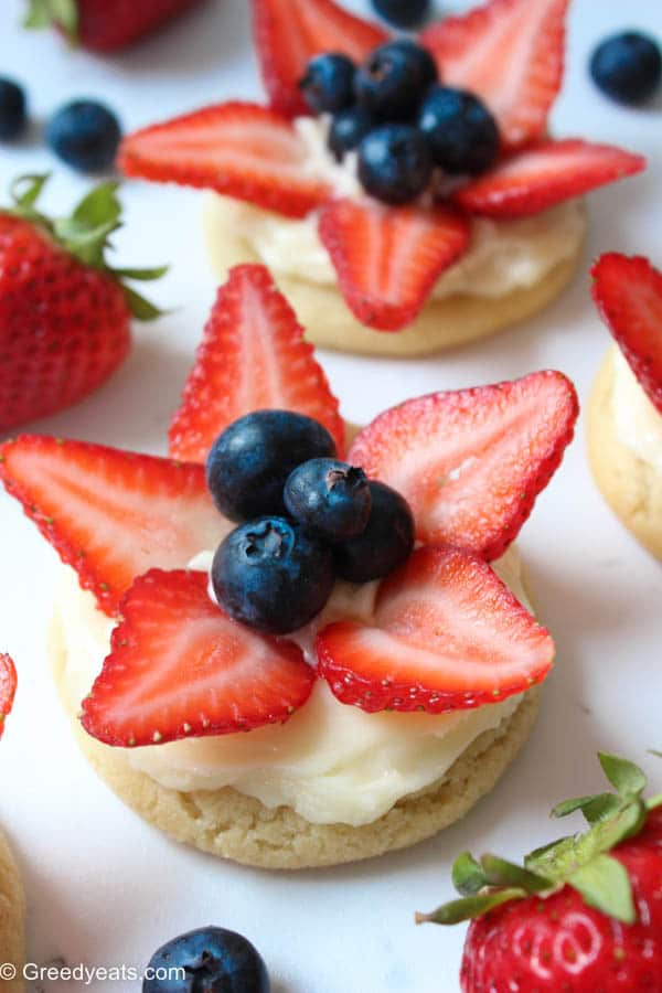 Mini version of a sugar cookie pizza! These mini fruit pizza sugar cookies are so chewy and refreshing from lemon cream cheese frotsing and fresh berries.
