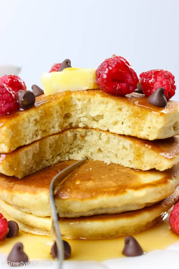 Oh-so-fluffy, quick and easy pancakes served with butter, raspberries, syrup and chocolate chips.