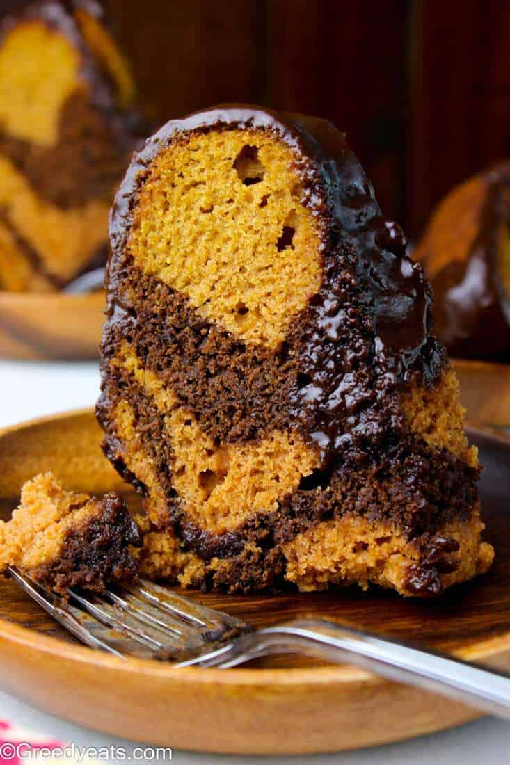 Tall, soft and tender Sweet Potato Pound Cake recipe with thick chocolate swirls inside. The bundt cake it topped with shiny chocolate glaze!