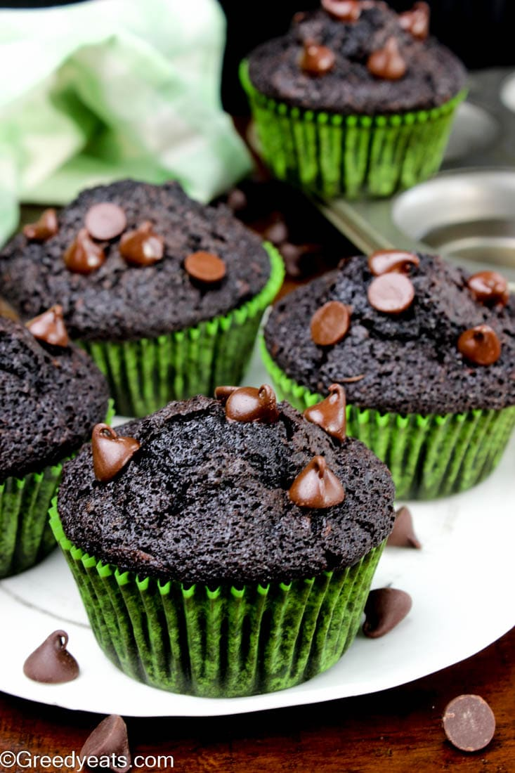 Five chocolate zucchini muffins with choc chips on a white plate.