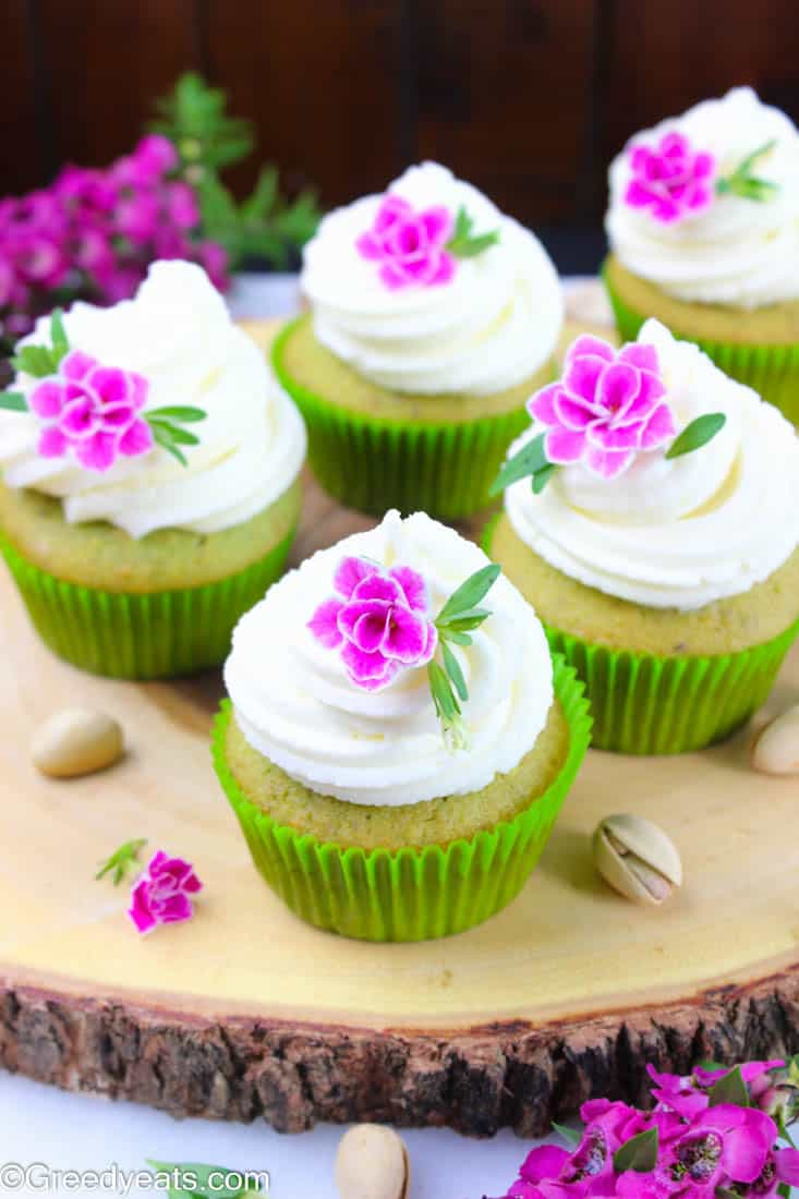Pistachio cupcake recipe scented with real pistachios flavor and piled high with fluffy vanilla frosting