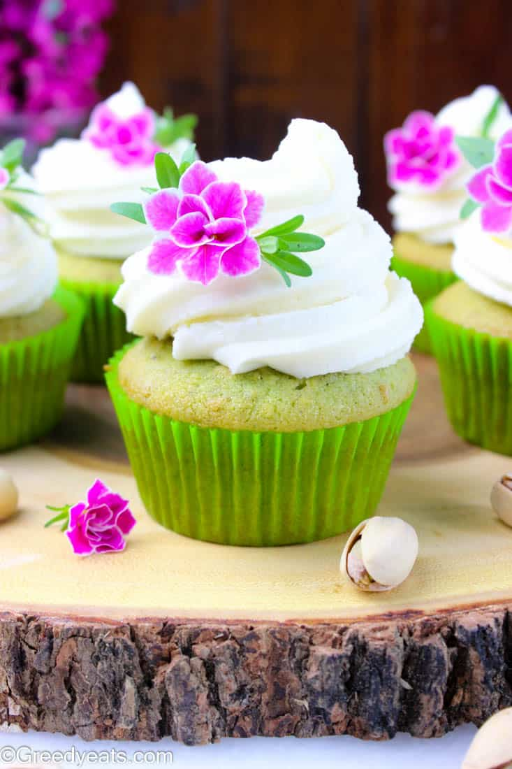 Soft and fluffy pistachio cupcakes frosted with creamy vanilla butter frosting