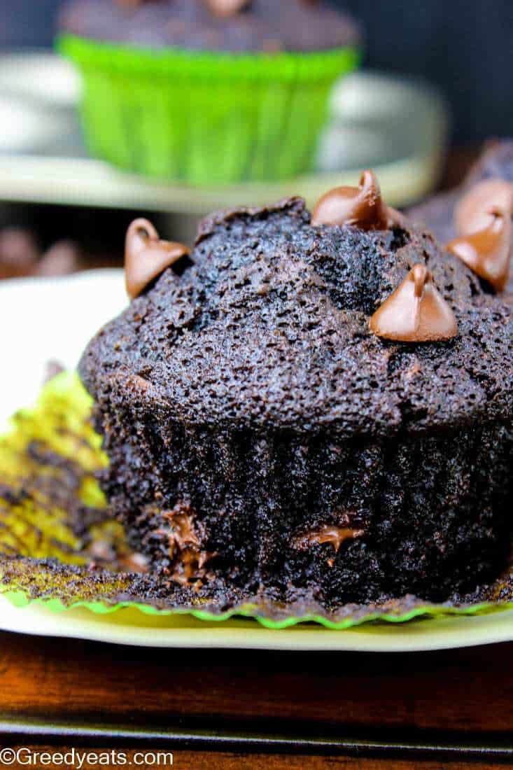 Moist and tall Zucchini Chocolate Muffin unwrapped on a plate.