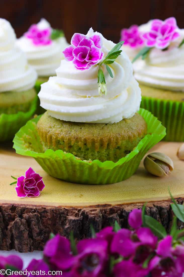 Easy pistachio cupcake recipe with real pistachio crumbs, sour cream and cake flour. These are frosted with dreamy vanilla buttercream.