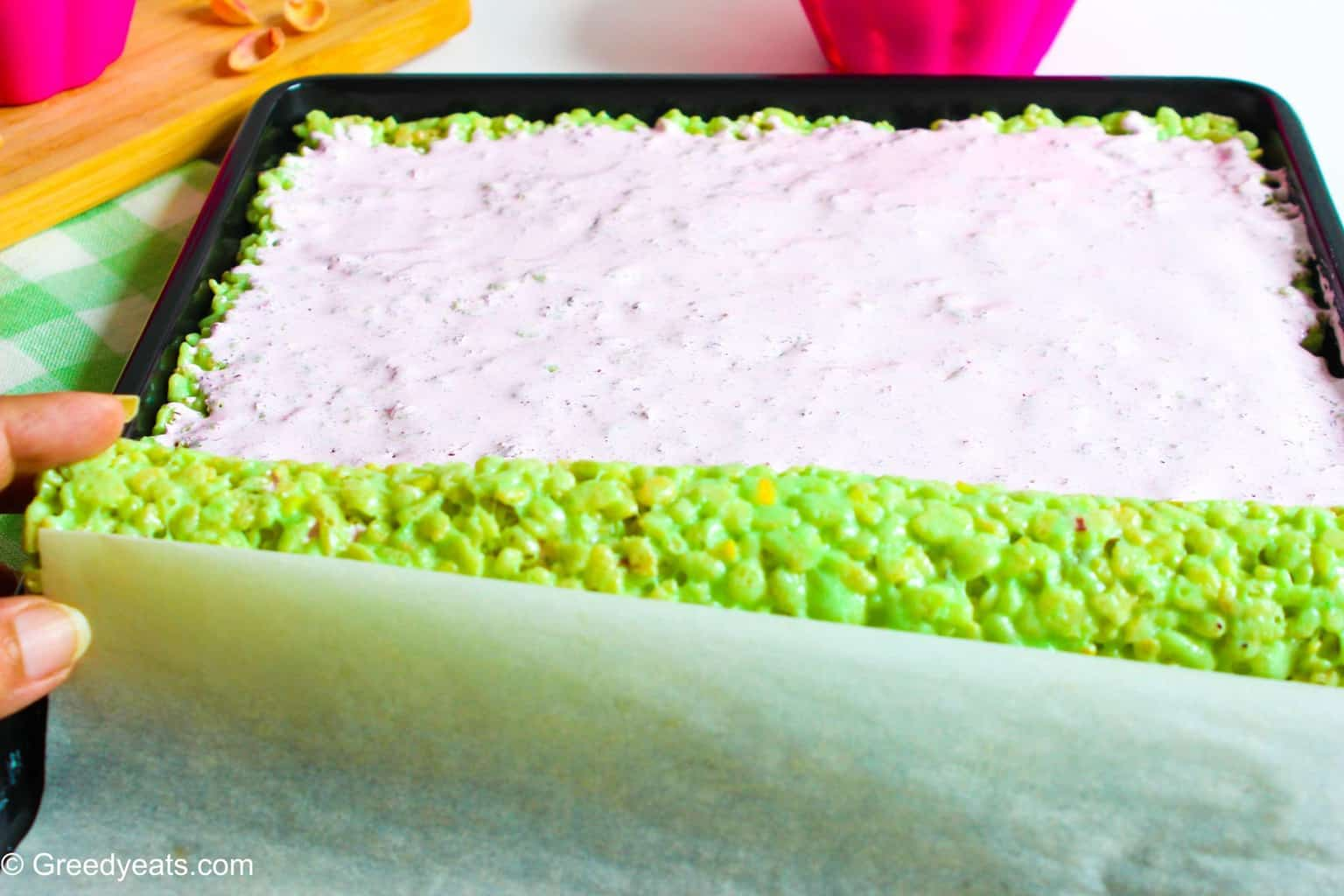 Rolling rice krispie treats with the help of parchment paper.