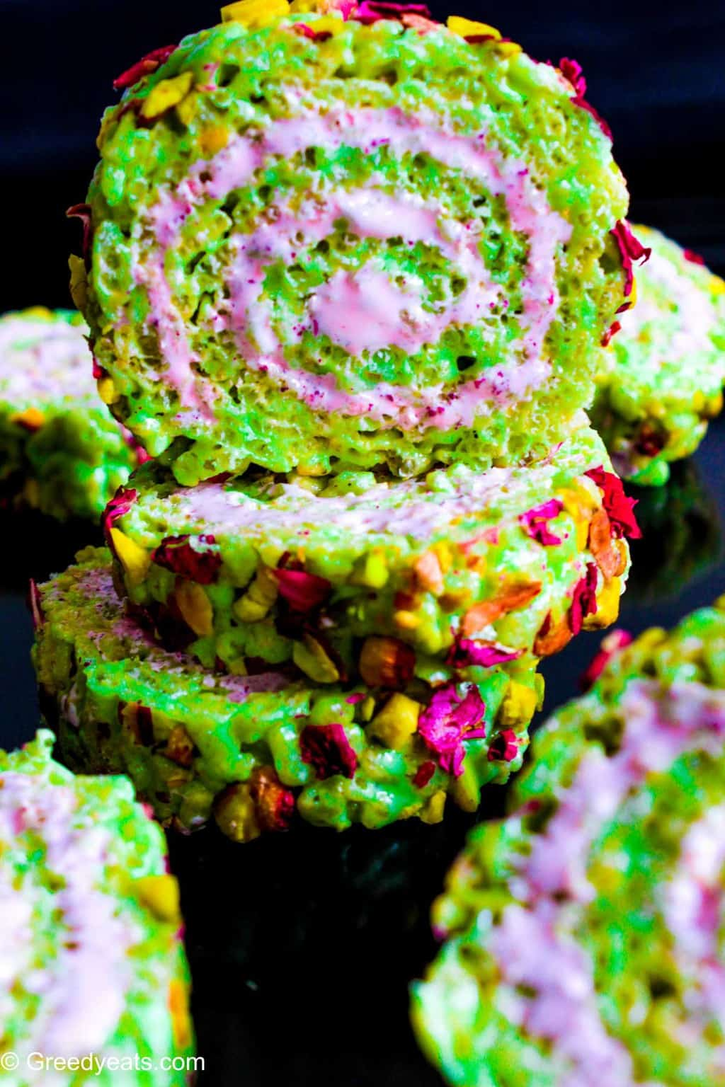 Easy Rice Krispie Treat slices swirled with marshmallow fluff and topped with real pistachio chunks.