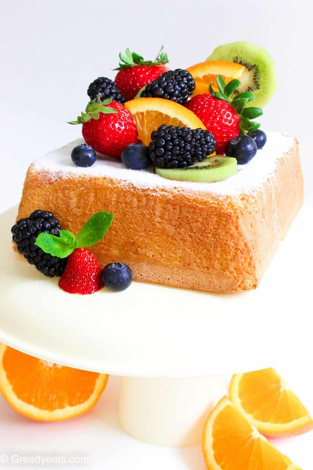 Small Lemon Sponge Cake topped with icing sugar and fresh fruits.