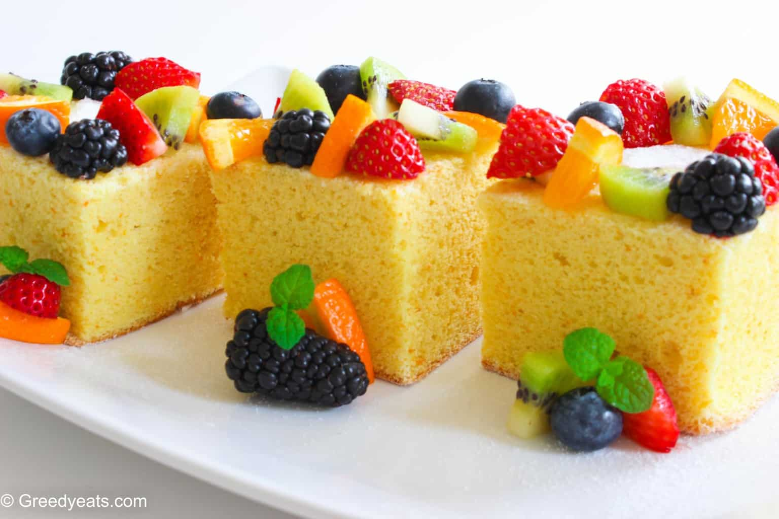 Pieces of small lemon cake that are spongy, soft and fluffy topped with fresh fruit.