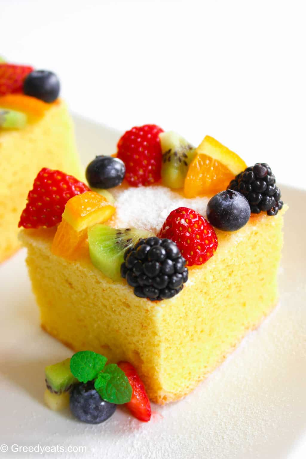 A slice of fluffy lemon cake topped with confectioners' sugar and fresh fruit toppings.