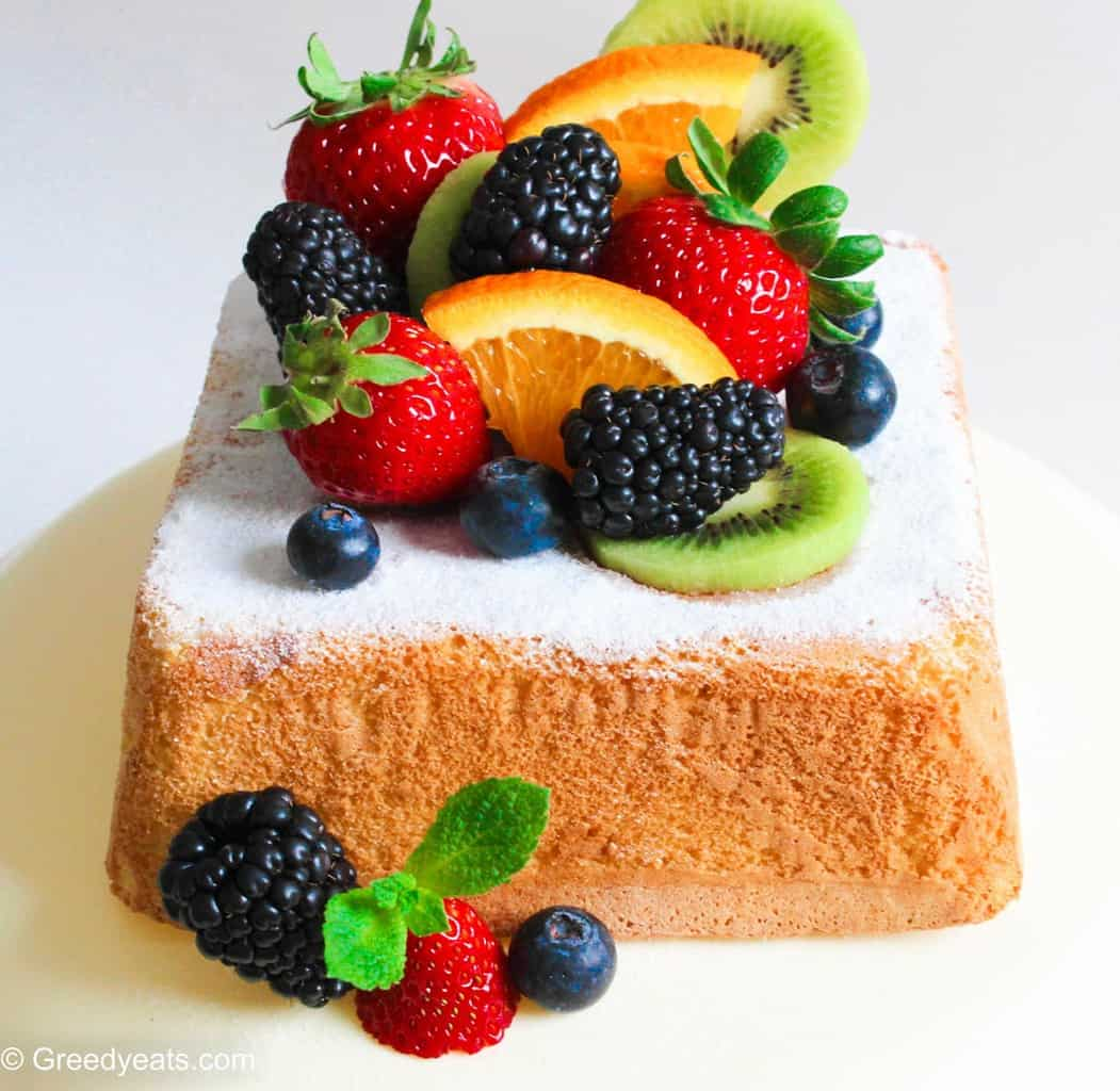 Soft and fluffy Lemon Cake topped with icing sugar, berries, kiwi and oranges