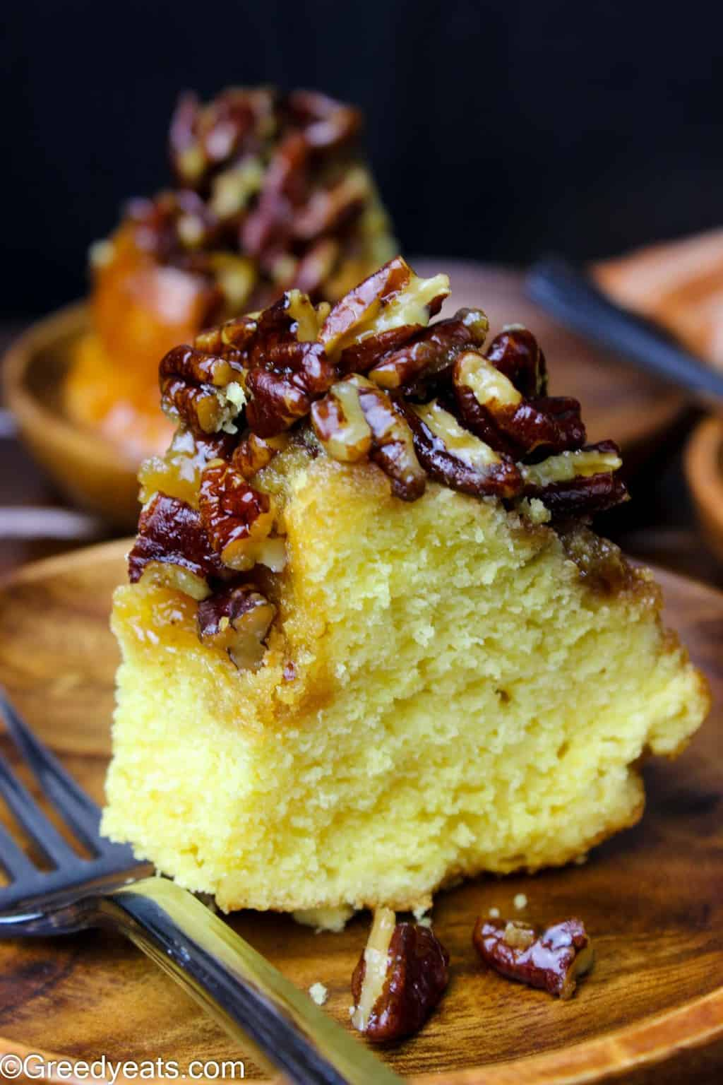 Buttery pound cake with sticky and caramel-y pecan filling slice on wooden plate.