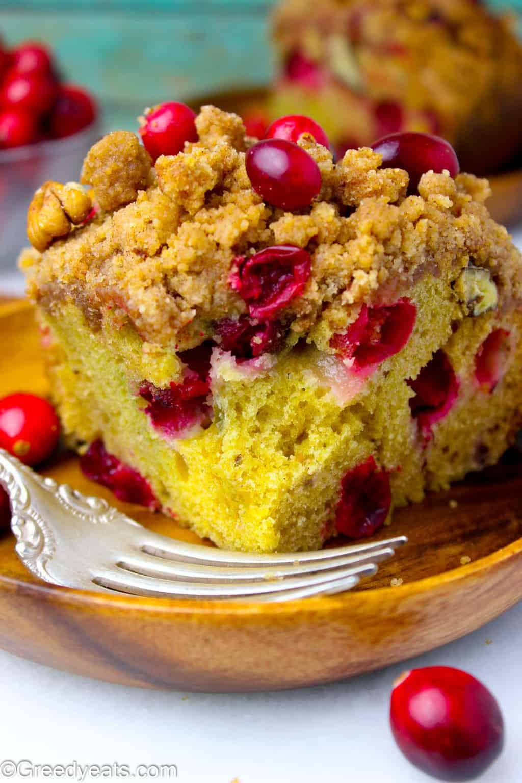 Soft and Buttery orange flavored Cranberry Coffee Cake slice on wooden plate.
