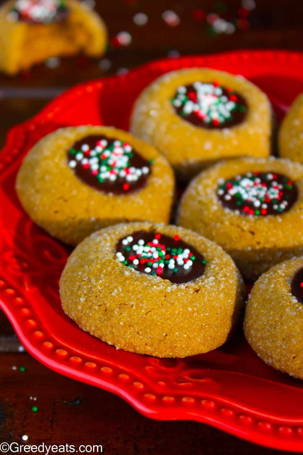 Molasses thumbprint cookies with chocolate ganache and christmas sprinkles.