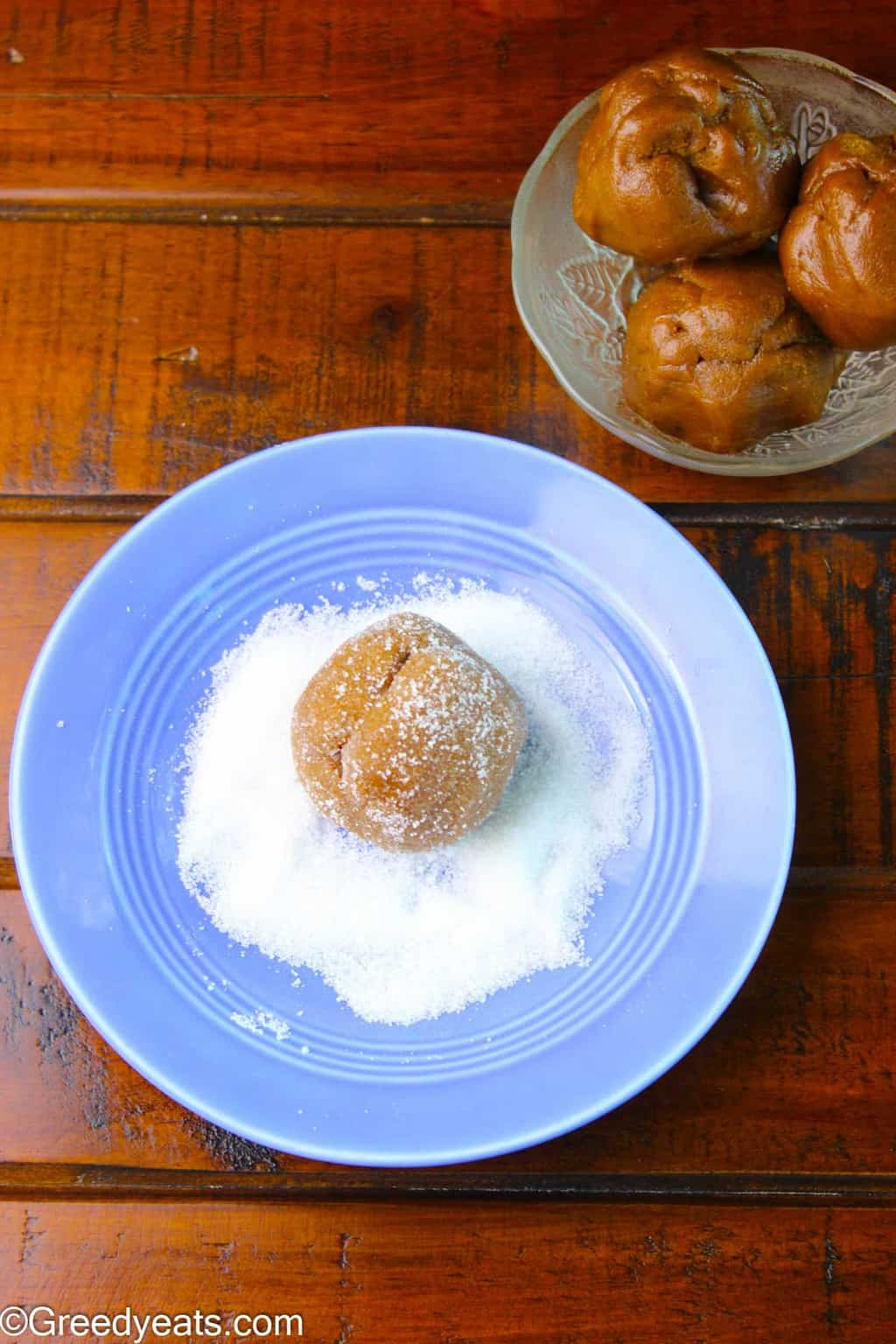 Molasses cookie dough balls rolled in granulated sugar.