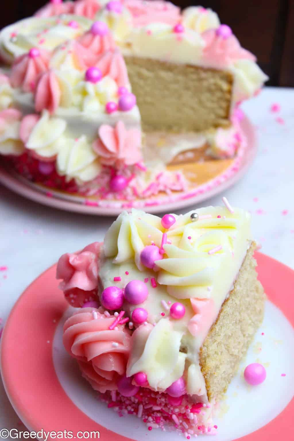 Easy vanilla cake slice with creamy white and pink vanilla buttercream frosting recipe on Greedyeats.com