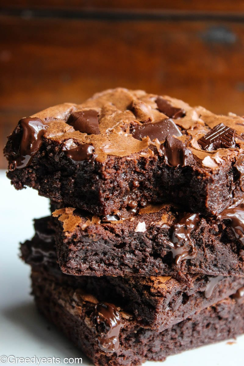 A close up shot of moist and gooey brownies stacked on each other.