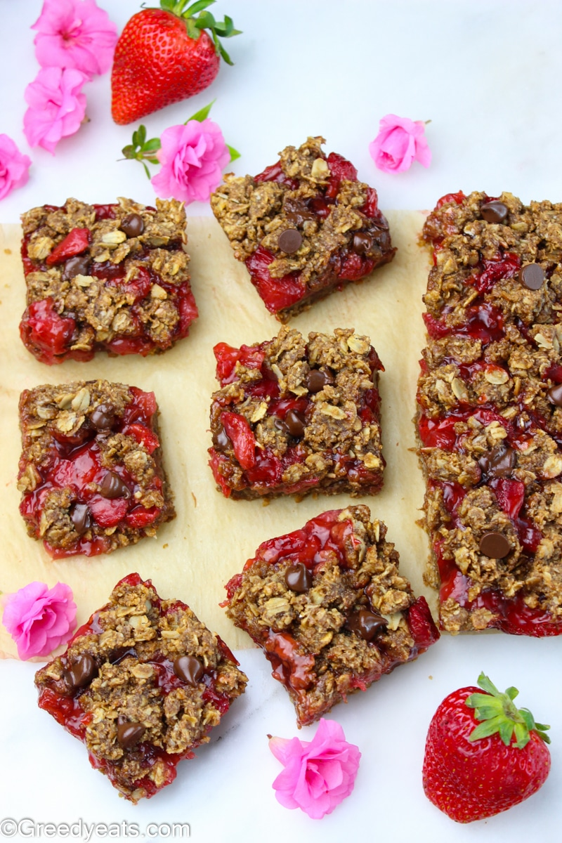 Wholesome breakfast bars squares on a parchment paper with fresh strawberries.