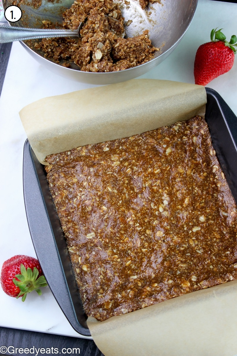 Oats mixture layered in lined baking pan.