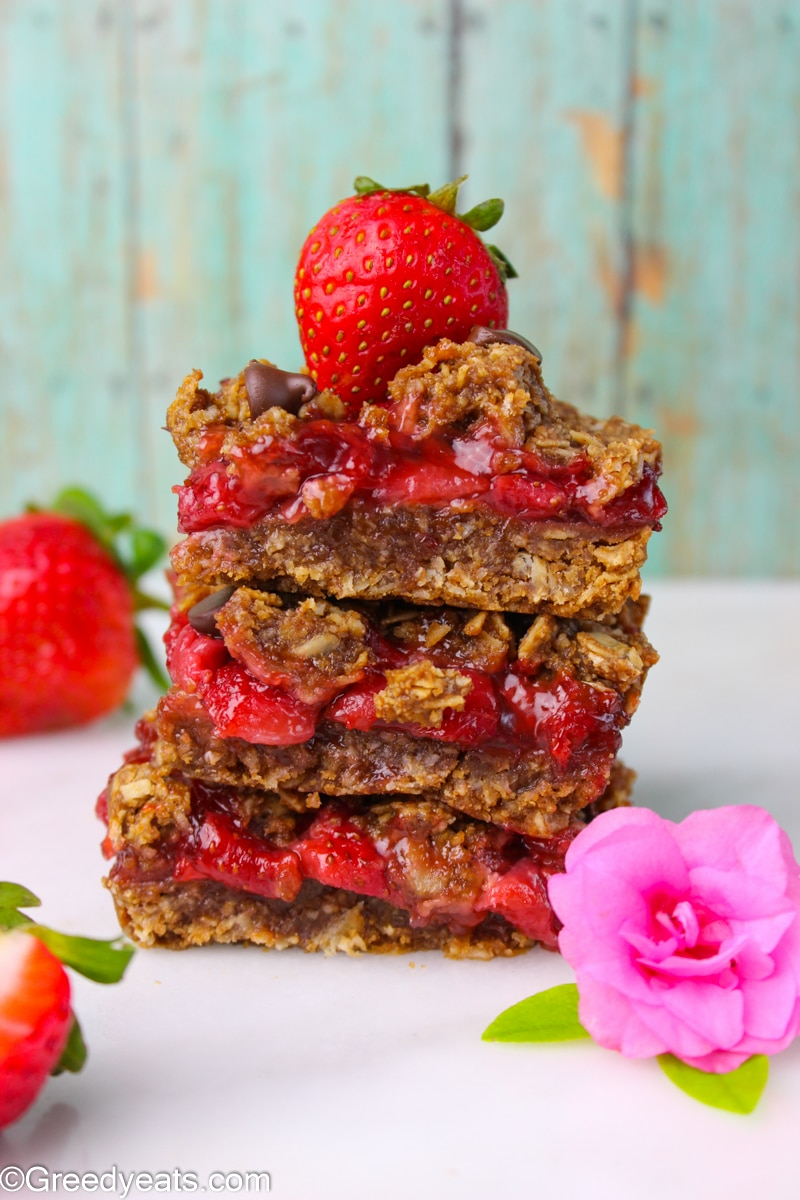A stack of chewy Strawberry Oatmeal Bars layers with fresh strawberry filling.