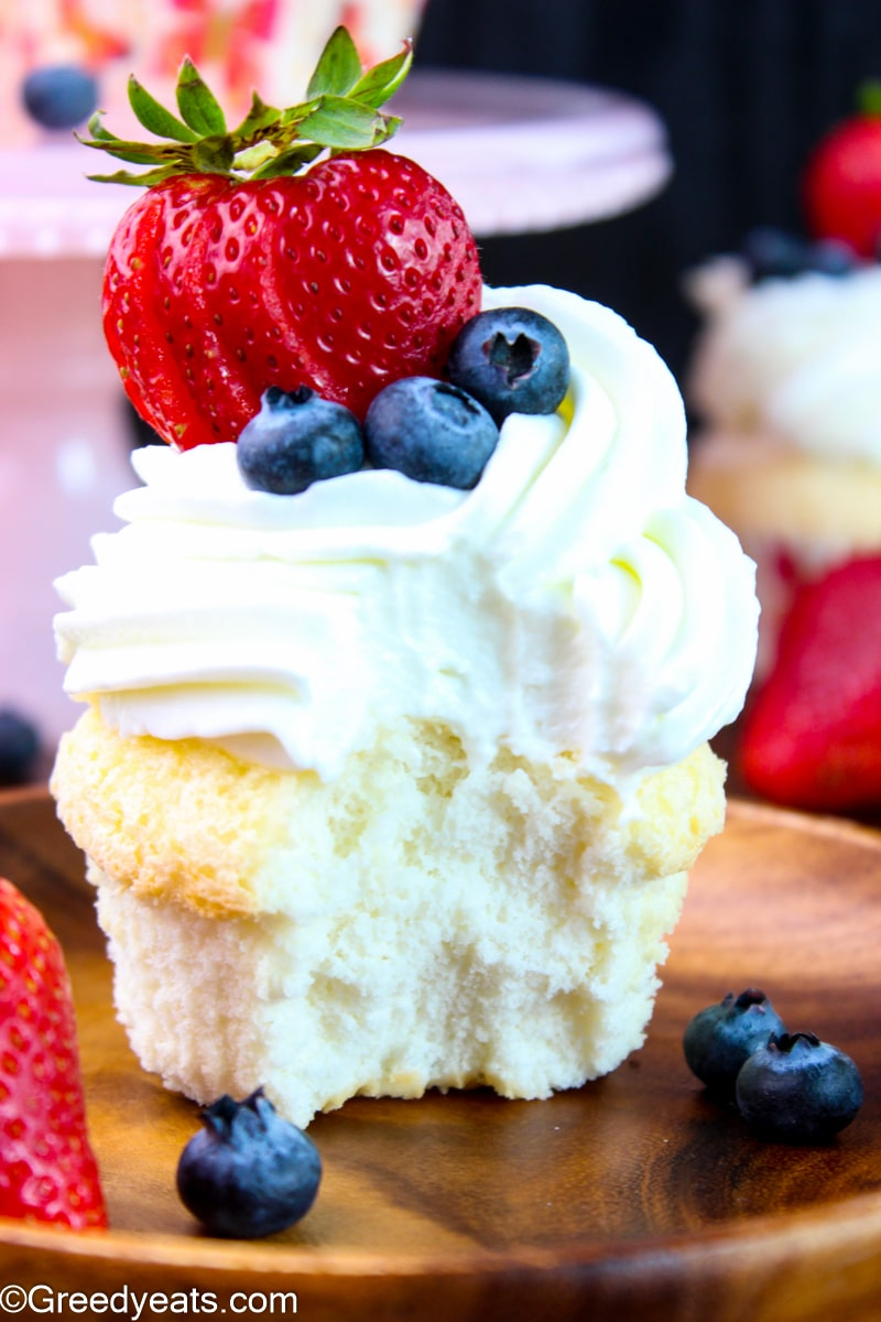 Delicate and fluffy Angel Food Cupcakes topped with whipped cream and fresh fruit toppings.