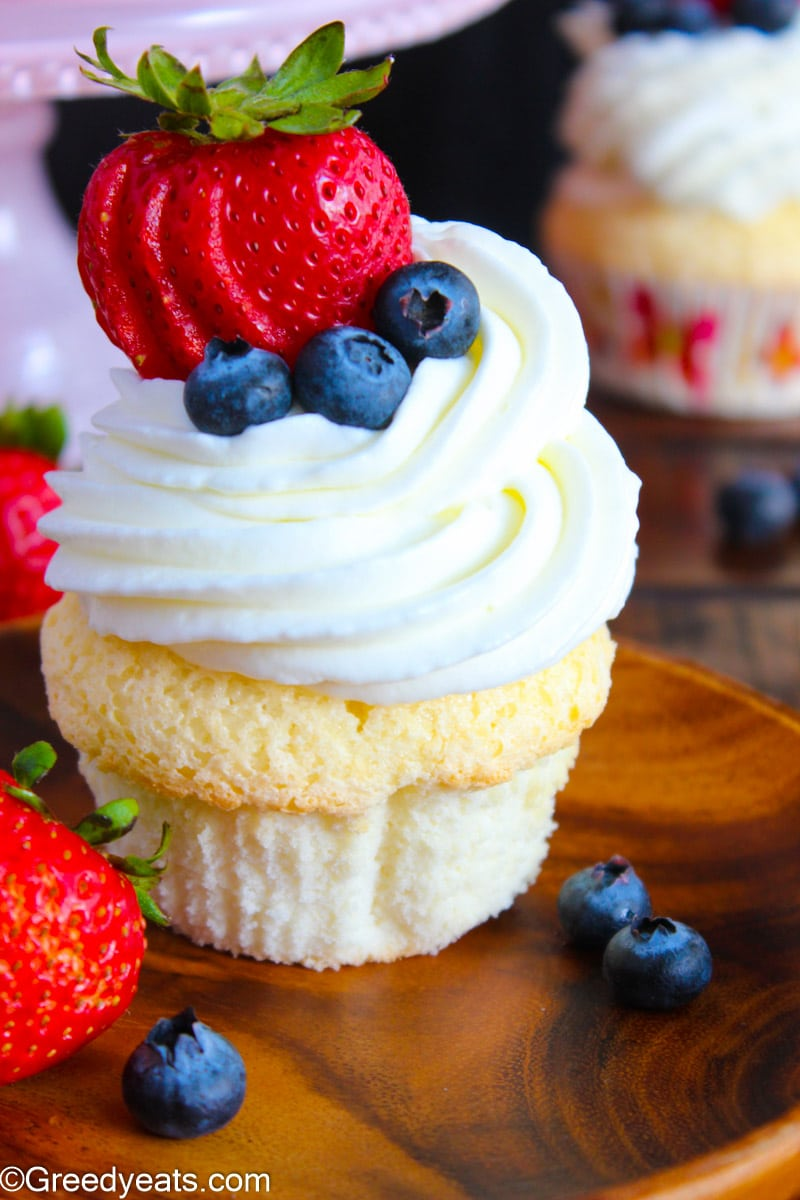Light and soft Angel Food Cake Cupcakes topped with whipped cream topping.