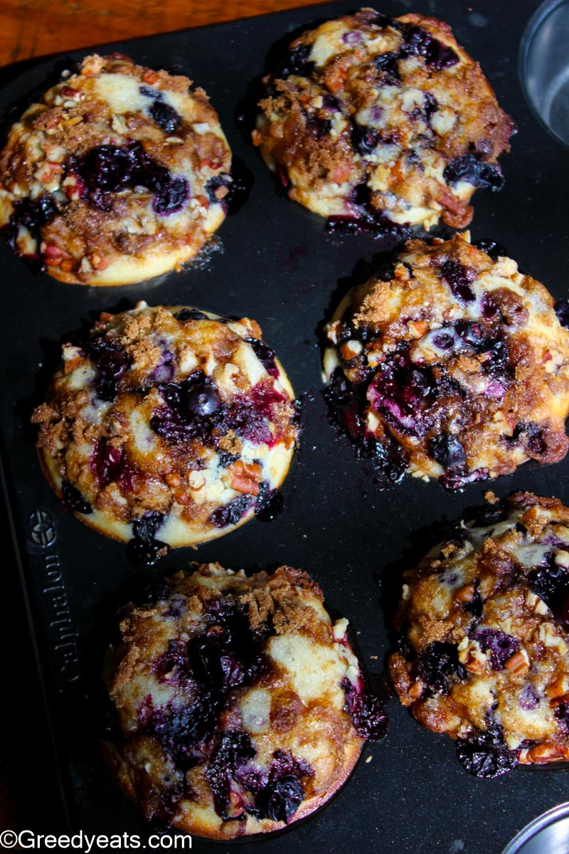 Tall and moist blueberry muffins topped with crunchy streusel, cooling down in a muffin pan.