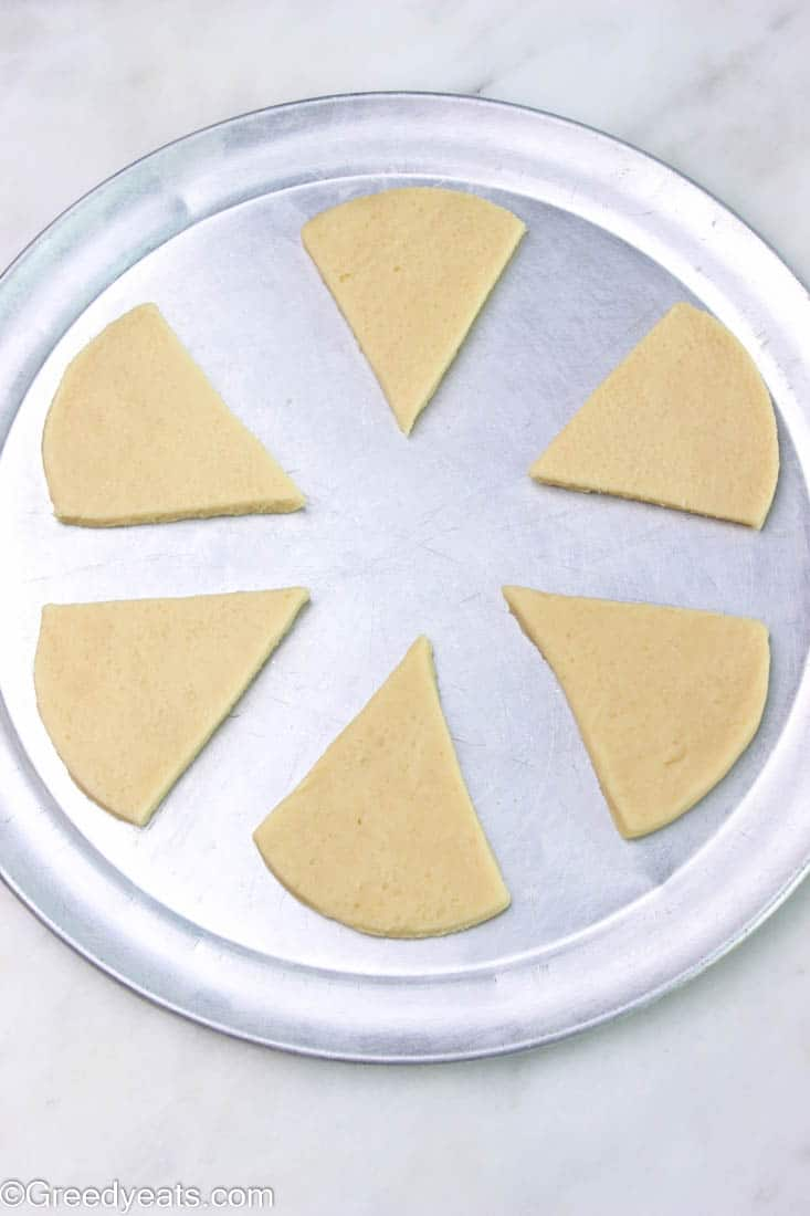 Sliced and unbaked sugar cookies on a plate