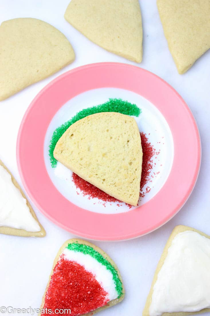 Decorating sugar cookies by dipping them in sanding sugar.