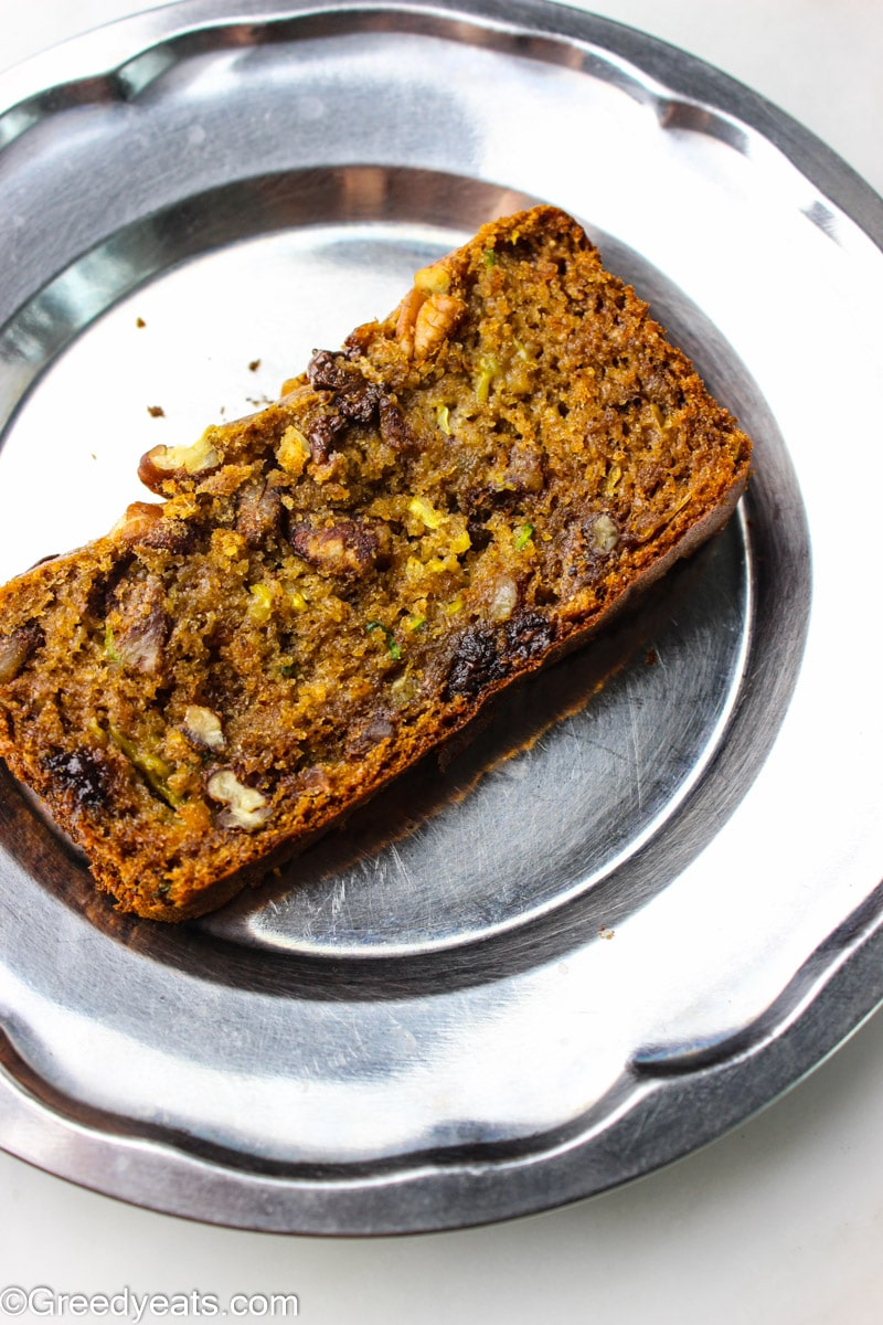 A slice of moist and flavor packed zucchini bread kept on a steel plate.