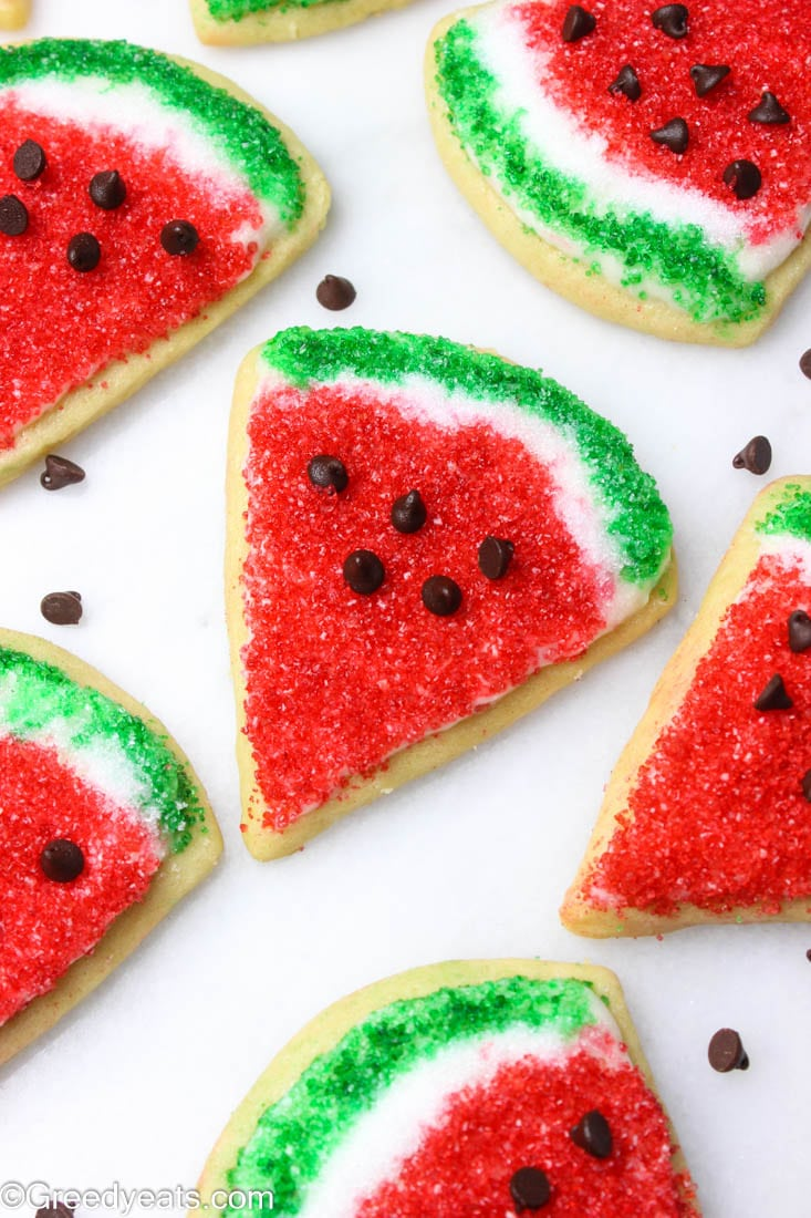 Cut out sugar cookies in the shape of watermelon cookies on a white board.