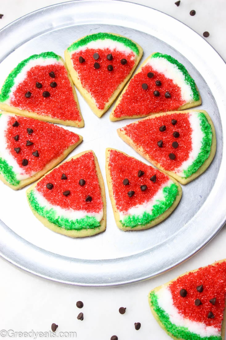 Watermelon sugar cookies with mini chocolate chip seeds arranged on a plate.