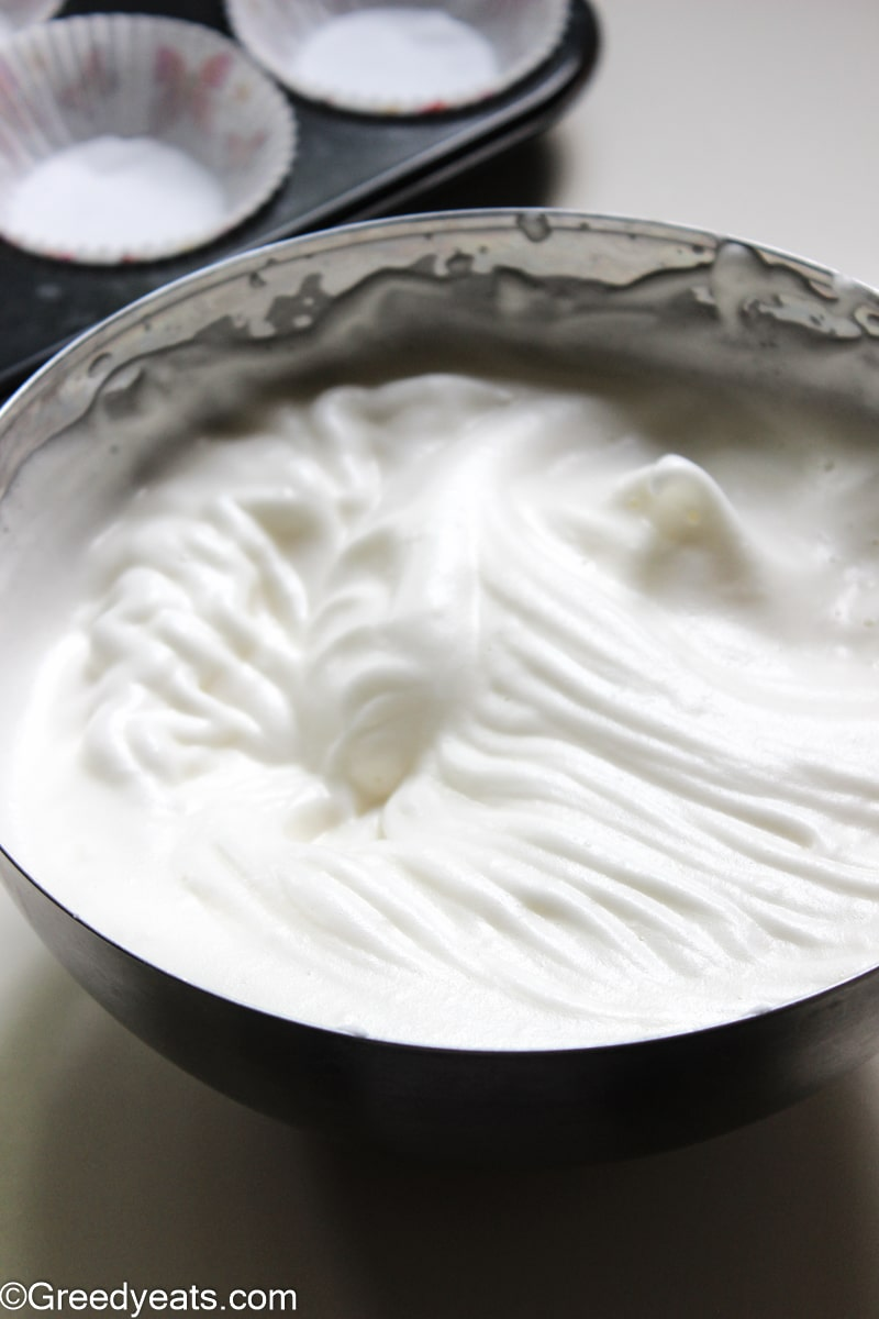 Whipped egg whites to stiff peaks in a mixing bowl.