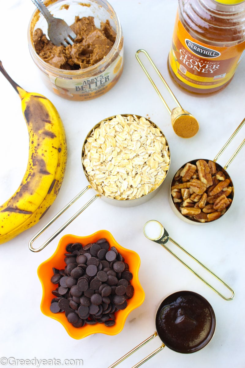 Ingredients to make healthy breakfast cookie recipe like honey, almond butter, banana, chocolate chips, oats and pecans.