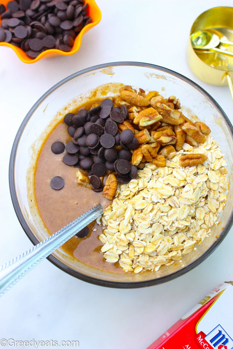 Ingredients like oats, nut butter, pecans and chocolate chips in a mixing bowl