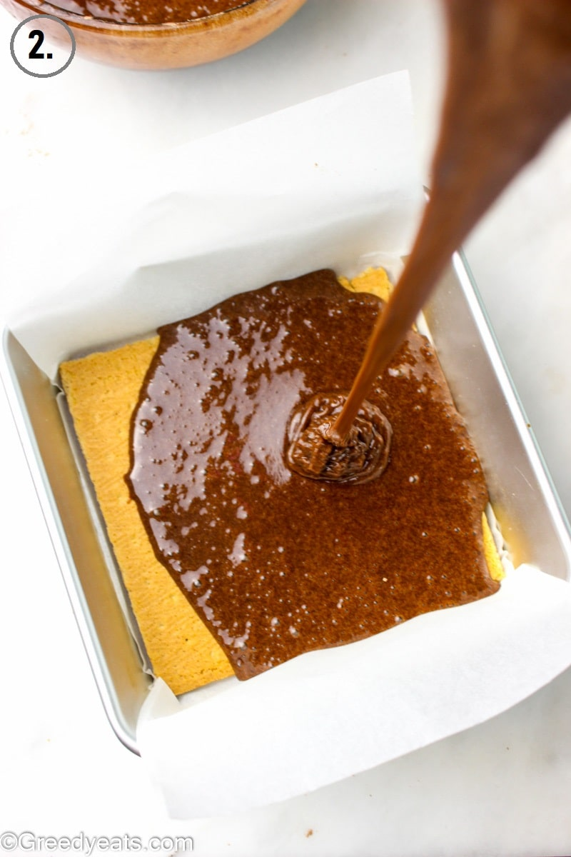 Pouring brownie batter over graham cracker sheets in a 8x8 square pan.