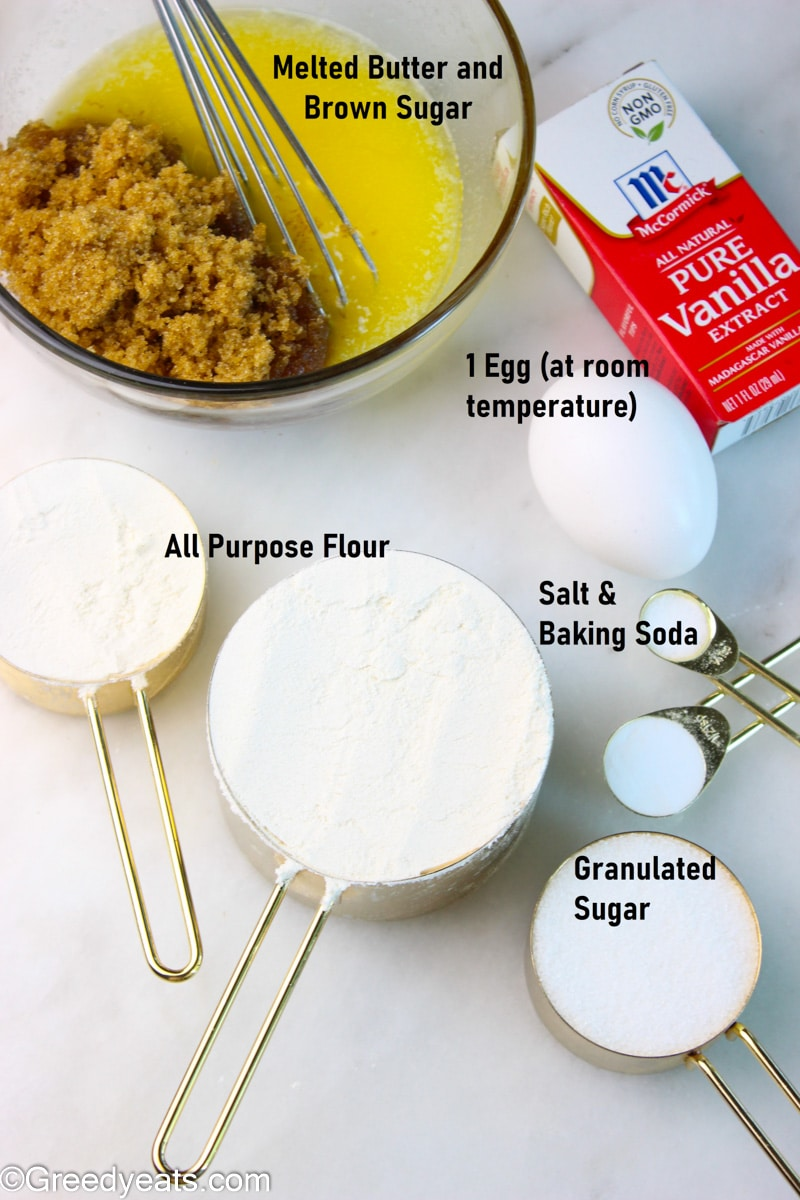 Ingredients like flour, leavener, egg, sugar, vanilla and salt in measuring cups, spoons and mixing bowl.