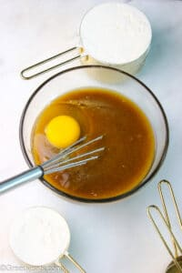 Melted butter, egg and brown sugar whisked in a mixing bowl with a whisk.