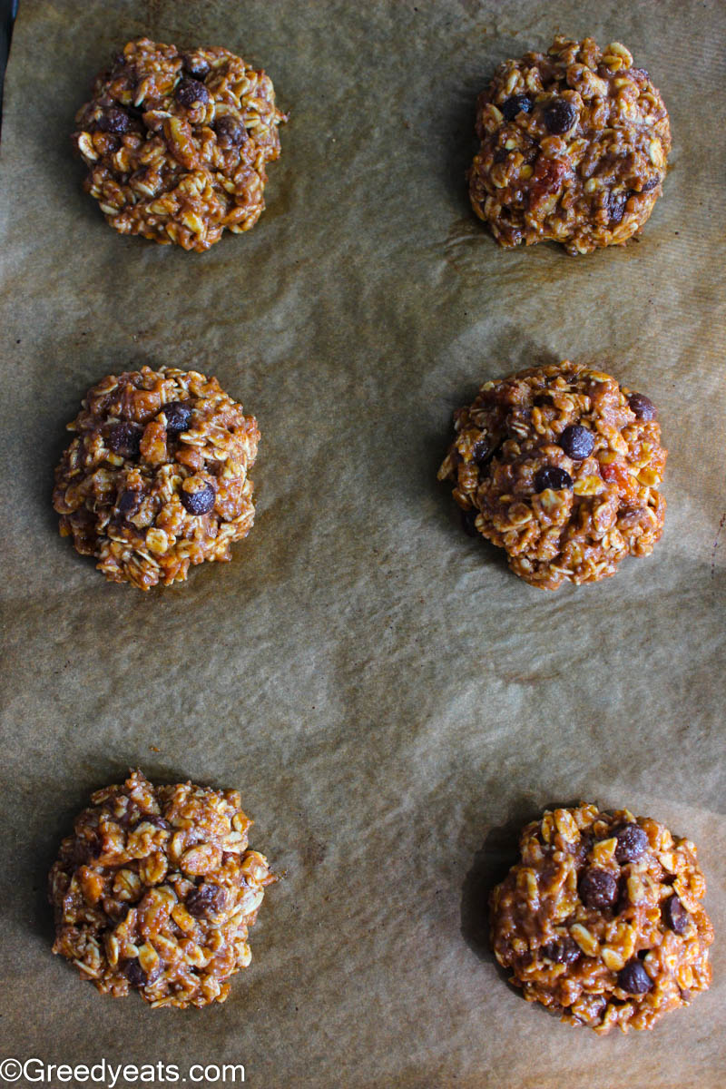 Healthy Breakfast Cookies loaded with nuts, oats, honey, banana and chocolate chips on a parchment paper.