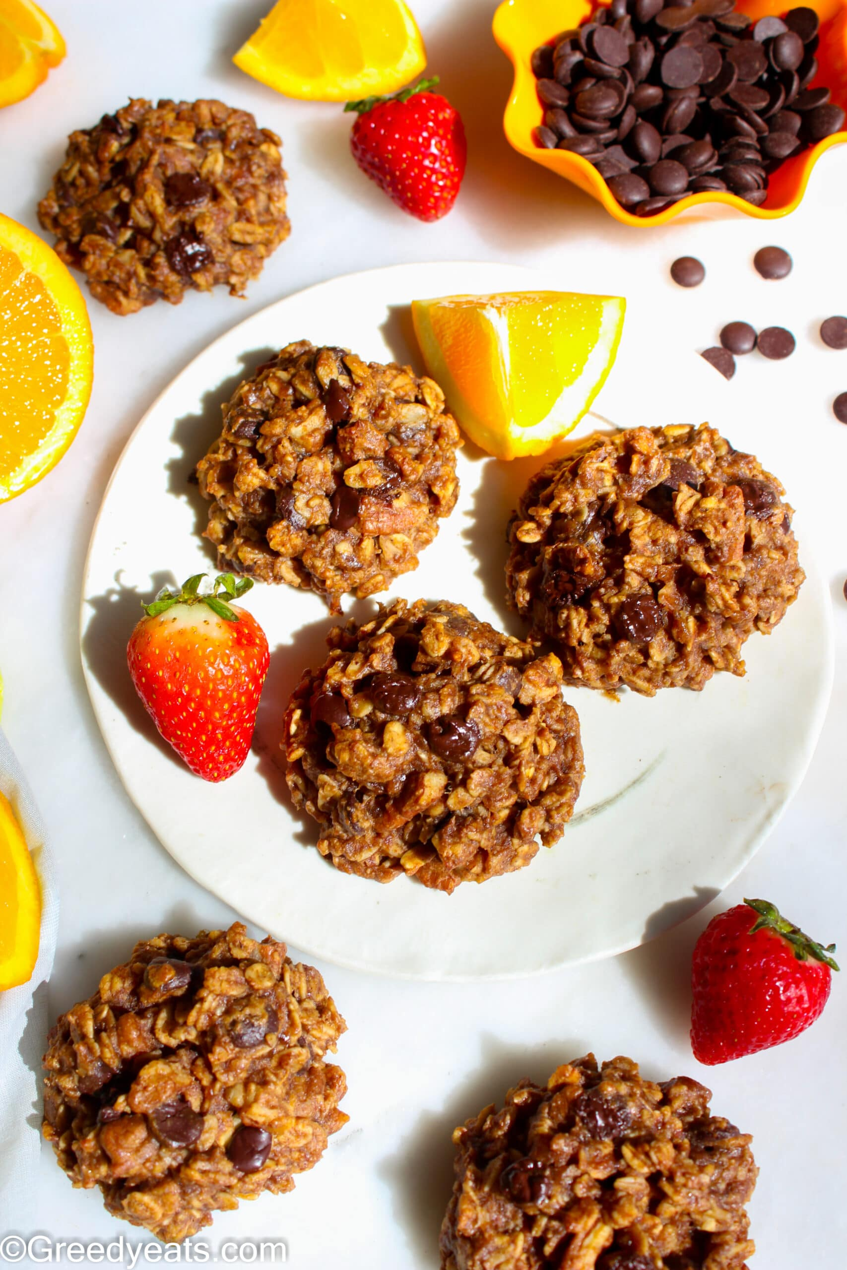 Thick and chewy Oatmeal Breakfast Cookies on a plate with chocolate chips and fresh fruits.