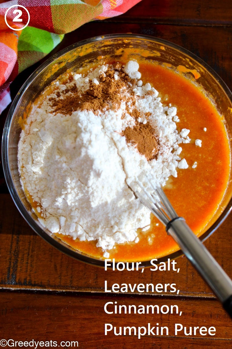 Dry ingredients over wet in a mixing bowl for pumpkin bars batter.